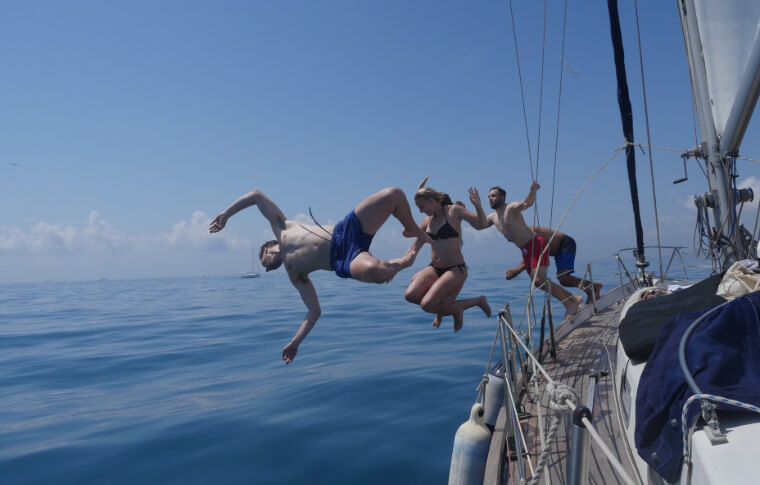 A group of 4 people jumping off a sailboat acrobatically in the refreshing ocean